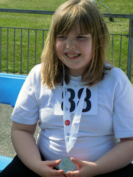 School pupil holding medal at athletics event