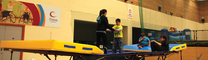 Rebound Therapy Instructor with disabled child on trampoline