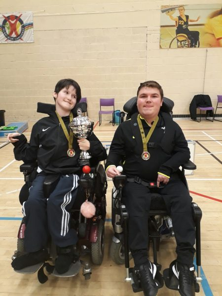 Two disabled children with their medals and cup