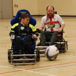 Two power wheelchair users playing power football