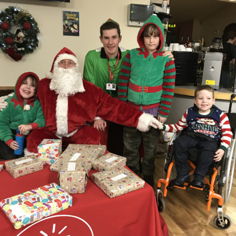 Santa with his elf helper and some of the children at the party